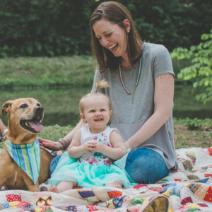 From left to right, a little red-and-tan pit bull mix in a blue striped bandana sits next to a one-year-old girl in a blue dress, and behind her is Maggie Marton, her mom, in a gray t-shirt and jeans.